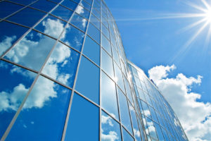 Image of the side of an office building with glass windows that reflect the blue sky and clouds above