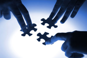 Image of three hands with their fingers pressing down on puzzle pieces.