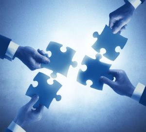 Image of four hands holding puzzle pieces that can fit together. This image is used as an example of the TaxWizard program.